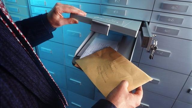 Ein Unbekannter legt ein Couvert in einen Banksafe.