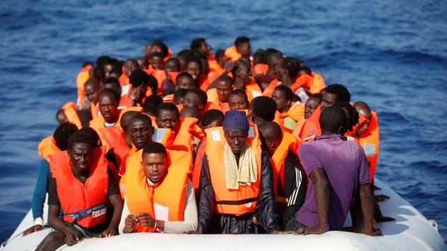 Eine Gruppe Schwarzafrikaner sitzt im Schlauchboot. Sie trägt orange Sicherheitswesten.