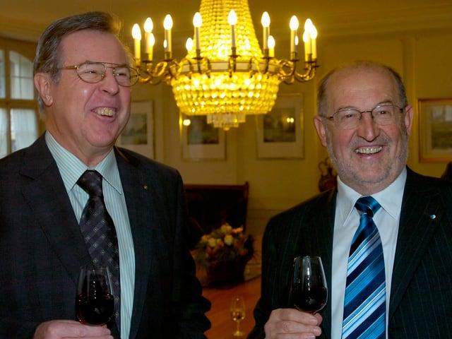 Zwei Männer mit Glas Wein, im Hintegrund Kronleuchter.