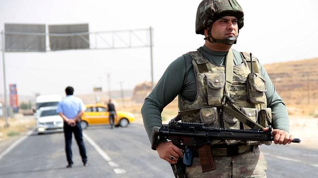 Soldat steht mit Gewehr auf Strasse im Vordergrund. Dahinter wartende Autos