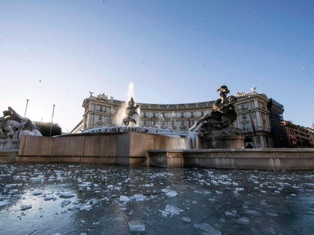Eisfläche, Brunnen, dahinter ein Gebäude.