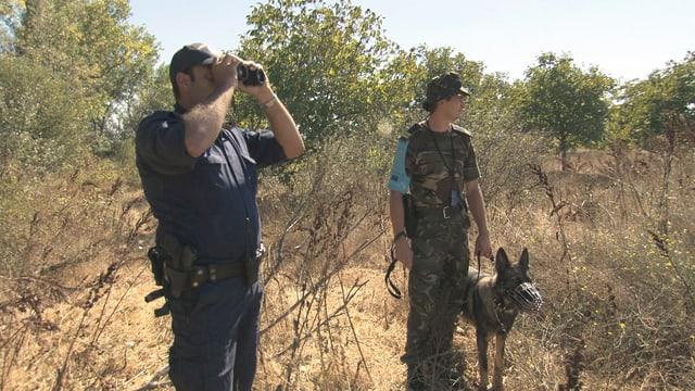 Zwei Grenzpolizisten mit Feldstecher und Hund in trockener Landschaft.