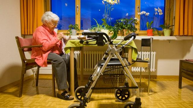 Die Bewohnerin eines Altersheims sitzt am Tisch in ihrem Zimmer
