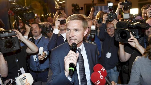 Ein Mann in Anzug und Krawatte, umringt von Medienleuten.