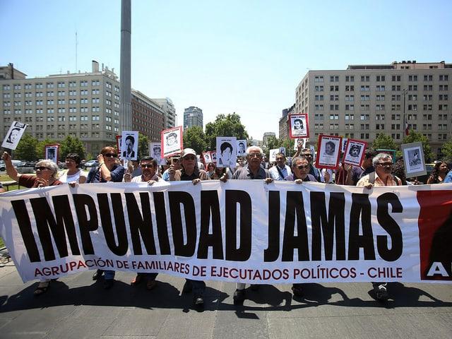 Demonstranten mit Schildern und einem Transparent mit der Aufschrift «Impunidad Jamas».