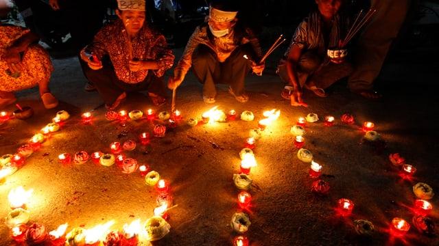 Betende vor der mit Kerzen formierten Zahl 370