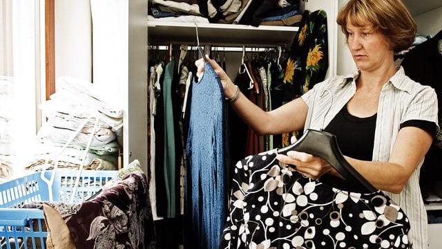 Frau prüft mit kritischem Blick den Inhalt ihres Kleiderschranks.