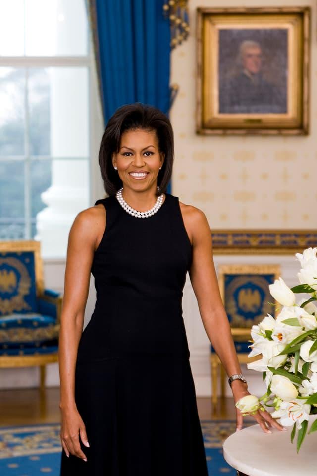 Michelle Obama an einem Tisch, der mit Blumen geschmückt ist, stehend in schwarzem Kleid und Perlenkette.