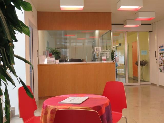 Im Vordergrund ein Tisch mit zwei roten Stühlen, dahinter der Empfang.