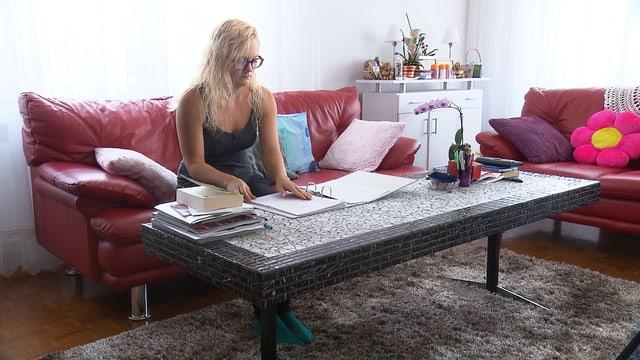 Eine Frau sitzt auf dem Sofa und studiert Unterlagen