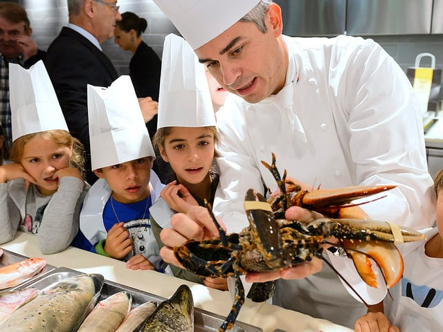Benoît Violier mit einem Hummer in der Hand, daneben stehen drei Fünftklässler mit Kochmützen und schauen ihm aufmerksam zu.