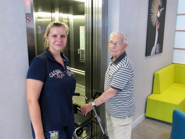 Eine Frau steht vor einem Lift neben einem älteren Mann mit grauen Haaren, der sich auf einen Rollator stützt.