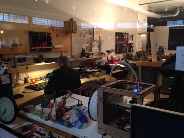 Blick durch das Schaufenster in eine Werkstatt. Ein Mann ist am Arbeiten.