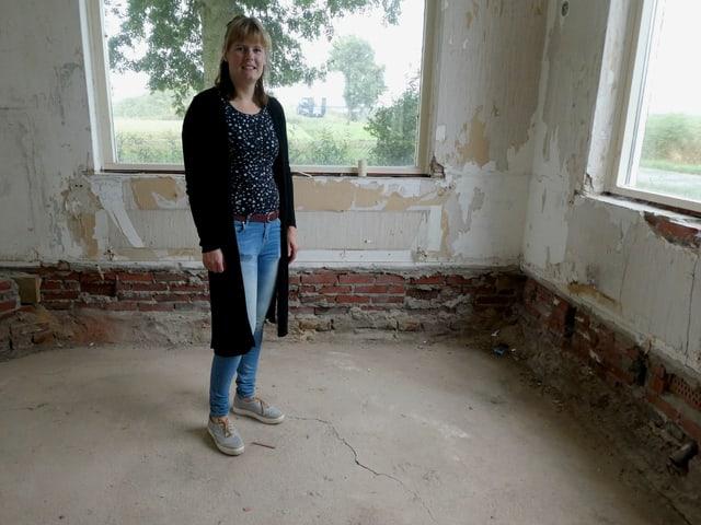 Ein Frau steht in einem Wohnzimmer, die Farbe von den Wänden abgeblättert, ein Riss im Boden.
