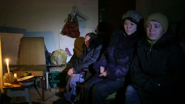 Drei Frauen sitzen in einem dunklen Bunker.