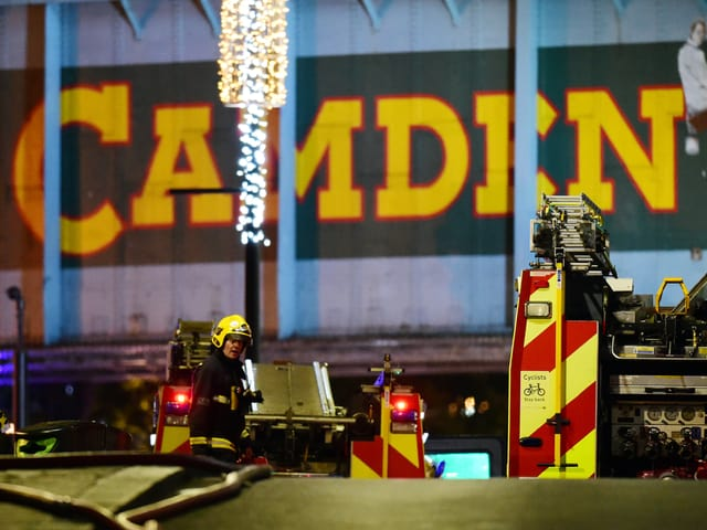 Feuerwehrmänner vor einem grossen Camden-Schild.