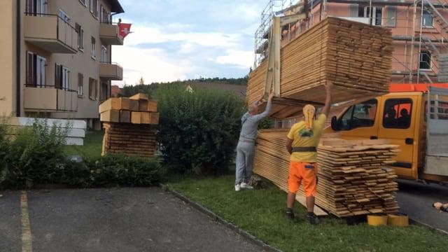 Zwei Männer laden Bretter mit einem Kran ab.