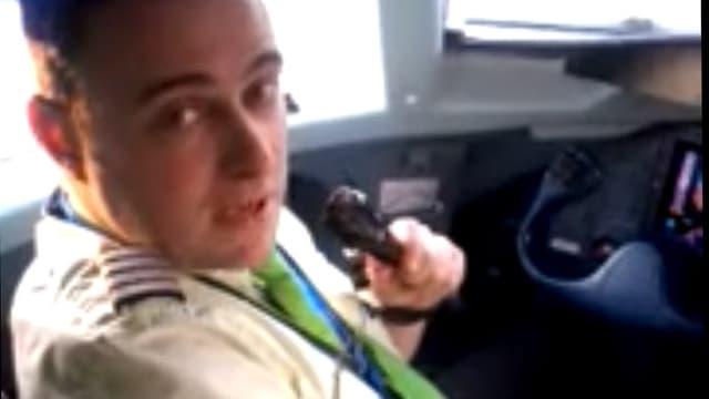 Pilot Tom Kreienbühl mit Mikrophon im Cockpit seines Flugzeugs