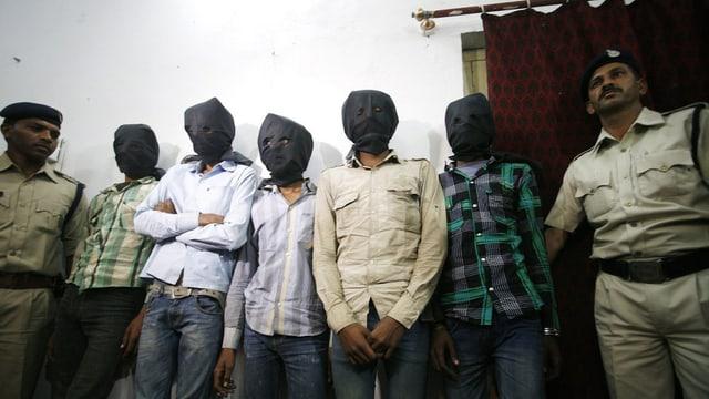 Täter werden von der Polizei vermummt vorgeführt