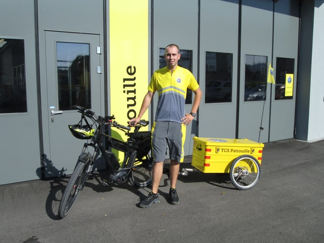 Patrouilleur in TCS-Klamotten und mit E-Bike und Veloanhänger.