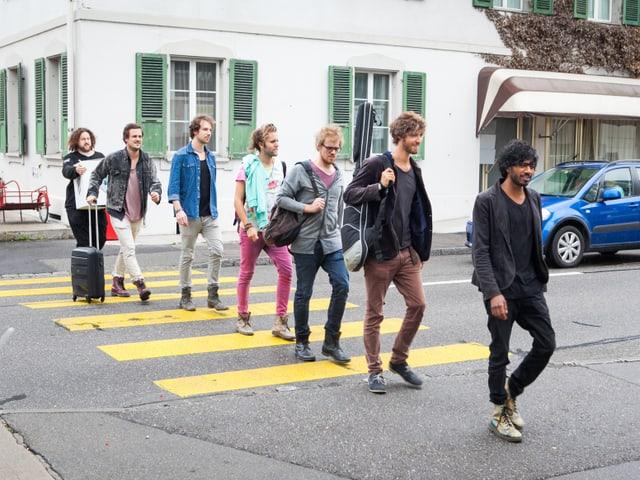 Die Musikgruppe «The Souls» und Moderator Daniel Bachmann gehen in einer Reihe über die Strasse. Sie sind unterwegs in den Proberaum.