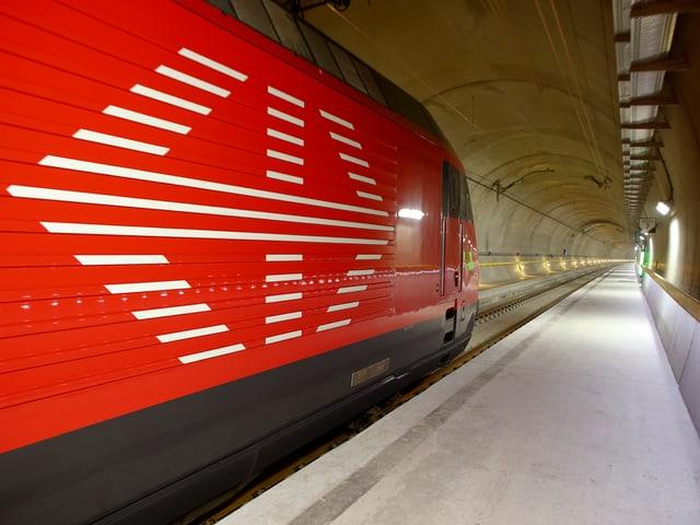 Blick in den 57-km-langen Gotthard-Basistunne, im Vordergrund eine rote Lok von der Seite.