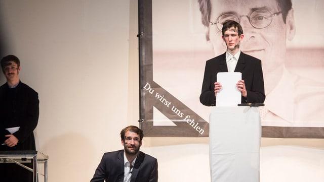Drei Männer in dunklen Anzügen auf einer Bühne.