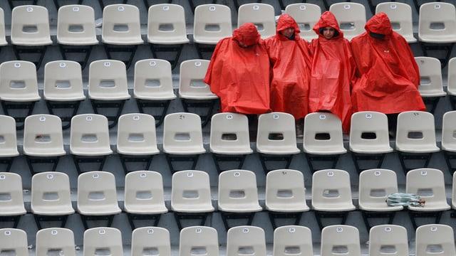 Vier Menschen sitzen in roten Regenjacken auf Zuschauertribünen.