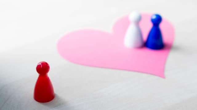 Zwei Spielfiguren stehen auf einem Herz, eine Dritte ist einsam daneben.
