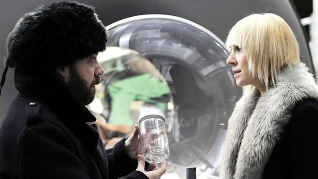 Ein Mann hält ein Glas in den Händen und spricht mit einer Frau.