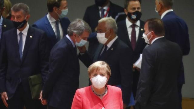 Merkel in rosa, im Hintergrund Männer in schwarz