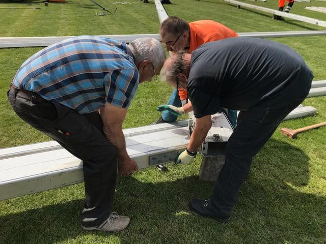 Drei Männer beugen sich über die Aluminiumpfosten