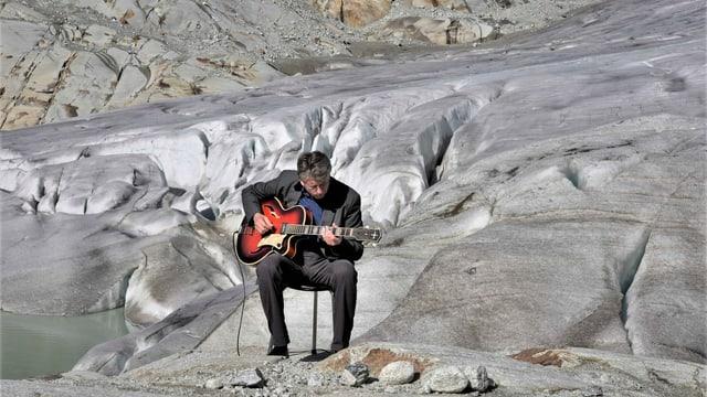 Ein Mann sitzt mit Gitarre an einem Gletscher.