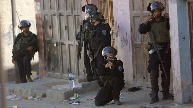 Soldaten, teilweise mit einem Gewehr im Anschlag
