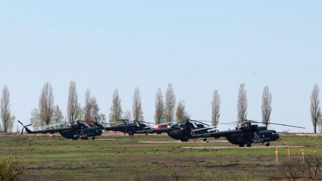 Fünf russische Militärhelikopter auf einem Feld in der Ukraine.