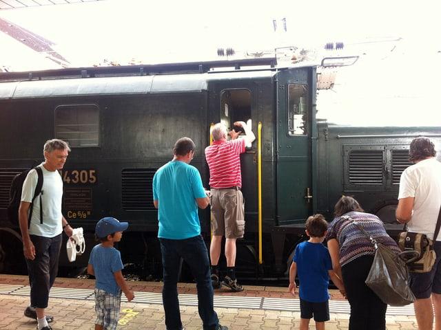 Menschen stehen auf dem Perron vor der Lokomotive.