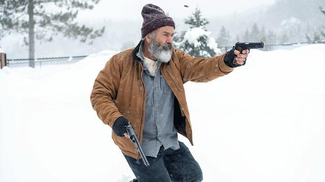 Ein Mann mit weissem Bart und Mütze rennt durch eine Schneelandschaft und schiesst mit zwei Pistolen.
