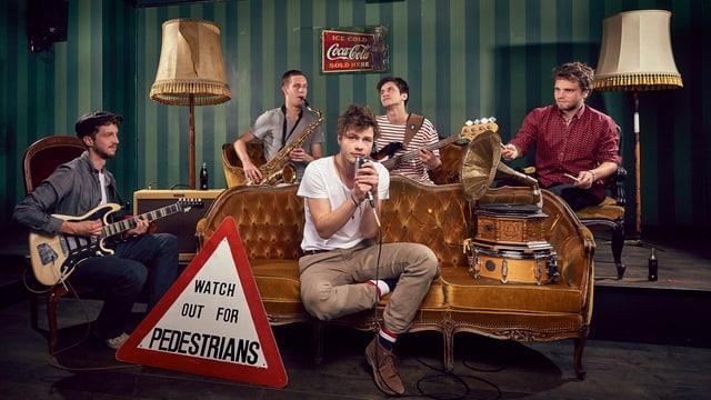 Fünf Jungs sitzen mit ihren Instrumenten auf diversen antiken Möbeln