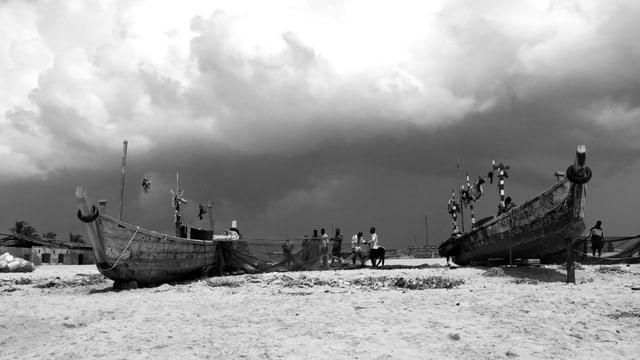 Schwarz-Weiss-Aufnahme: Stimmungsaufnahme mit bewölktem Himmel und einer grossen Sandfläche.