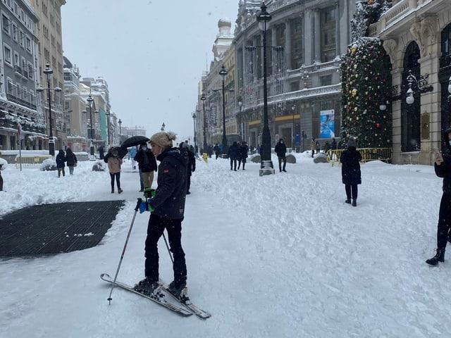 Ein Mann fährt in Madrids Strassen Ski.