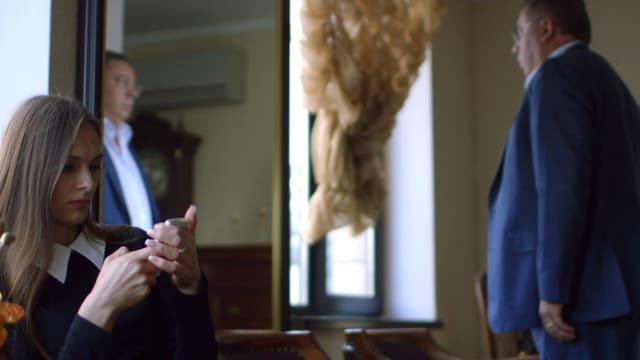 Olga sitzt und daddelt mit ihrem Smartphone und Konstatin schaut sich im Spiegel an.