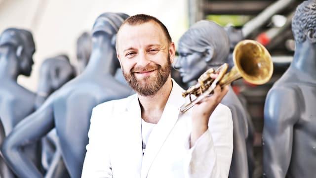 Mann vor Schaufensterpuppen mit Trompete.