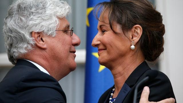 Philippe Martin, der abtretende Energieminister, lacht und umarmt Ségolène Royal.