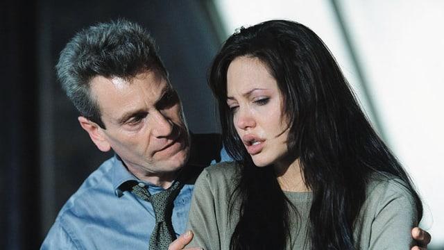 Ein Mann stützt eine Frau, die weint.