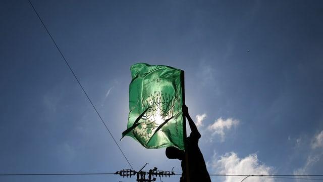 Symbolbild: Ein Mann hält eine grüne Hamas-Fahne vor die Sonne.