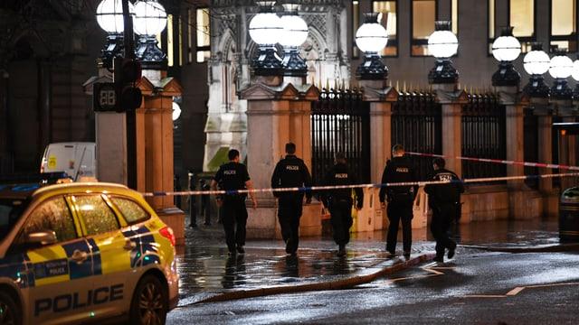 Fünf Polizisten gehen Richtung Bahnhof Charing Cross. Die Strasse hinter ihnen ist mit Absperrband gesperrt.