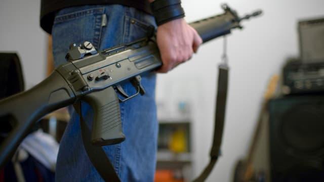 Ein Mann hält ein Sturmgewehr