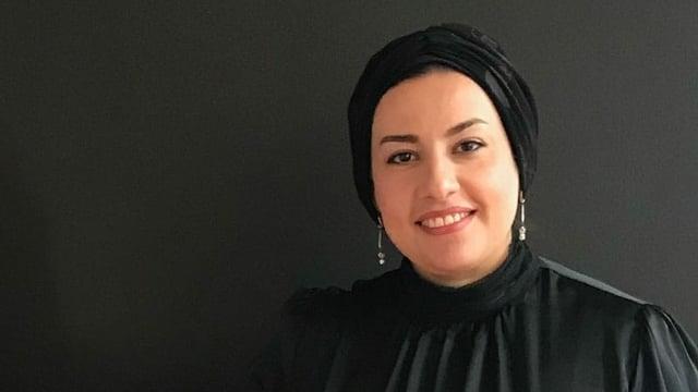 Eine Frau mit Kopftuch lächelt in die Kamera.