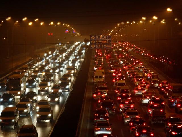 Von Smog verhüllte mehrspurige Strasse in Peking.