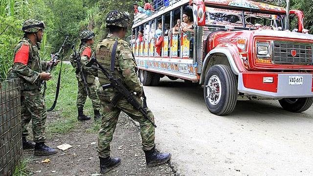 Kolumbianische Regierungssoldaten stehen an einer Dschungelstrasse. Ein farbiger Reisebus passiert die Patrouille.
